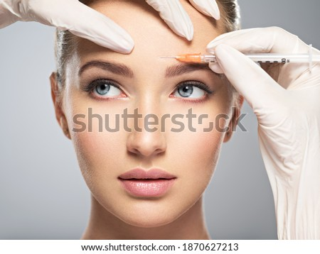 Portrait of young Caucasian woman getting cosmetic injection of botox  in forehead. Beautiful woman gets botox  injection in her face. Stock photo ©