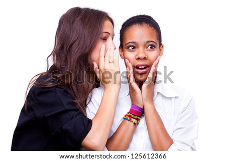 portrait of young caucasian woman telling a secret to an african american woman over a white background