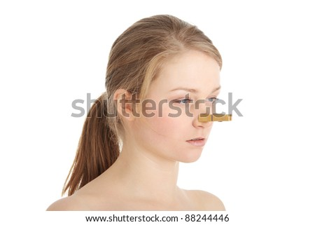 Portrait of young caucasian woman with Clothespin on her nose - bad smell concept