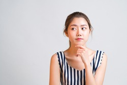 Portrait of young charming Asian woman looks pensive and curious thinking up and look sideways at grey background with copy space to the left, concept pensive thought woman, curious thinking woman.