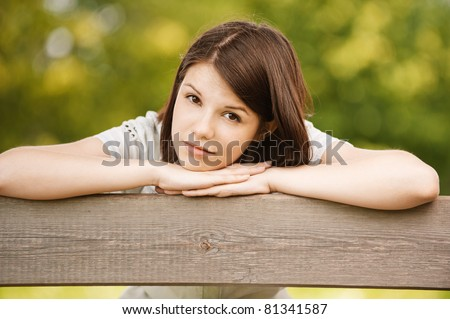 Portrait of young charming sad brunette woman with head laid on her arms at summer green park.