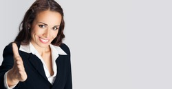 Portrait of young cheerful beautiful businesswoman giving hand for handshake, empty copy space place for some advertisement ad text, advertising or slogan, over grey background. Business concept photo