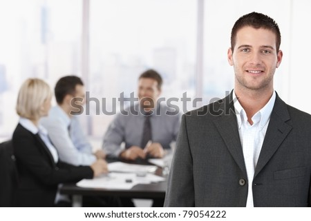 Portrait of young confident businessman in meeting room, with colleagues in background.?