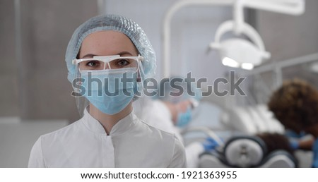 Portrait of young confident female dentist in protective cap, gloves and mask posing in dental office with assistants treating patient teeth on background