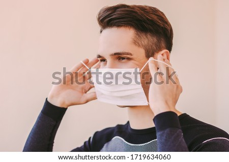 Portrait of young confident sports man listening music in wireless earbuds and putting on medical face mask. Happy sports man wearing protective mask and smiling. COVID-19 home quarantine training