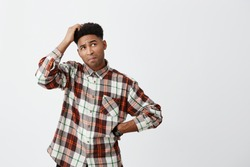 Portrait of young confused dark-skinned handsome man with afro hairstyle in checkered shirt holding head with hand, looking aside with satisfied expression, don't know what to do with debts