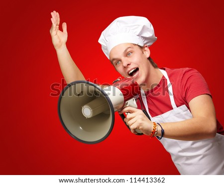 portrait of young cook man shouting with megaphone over red background