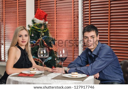 portrait of young couple about new year tree with glasses of wine