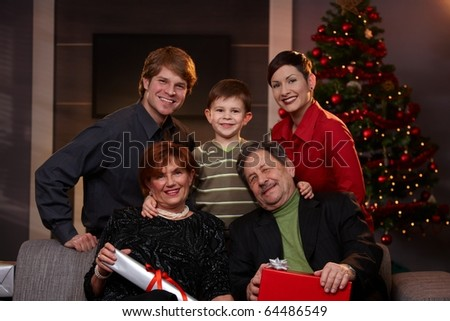 Portrait of young couple and son with grandparents at christmas, smiling. ?