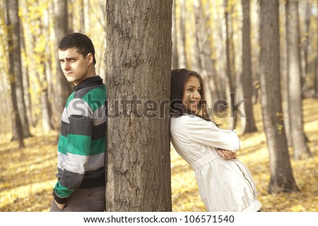 Portrait of young couple by tree  boy and girl spins rely on different sides in the trunk of a tree - a symbol of alienation separating misunderstanding of the difference argument insults