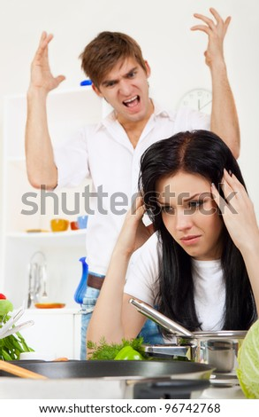 portrait of young couple conflict in their kitchen, relationship problem, negative emotion, aggressive man scream on woman, she is crying with tears on eyes