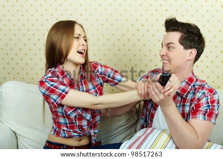 Portrait of young couple fighting beacause of remote control