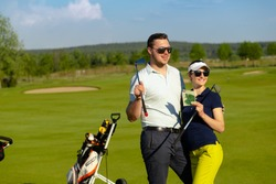 Portrait of young couple golfers are standing together in sportwear and sunglasses, holding golf clubs and happy smiling at gold course. Luxury lifestyle concept.