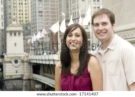 Portrait of young couple grinning withÃ?bridge behind them