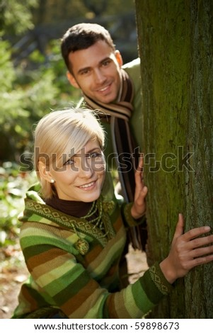 Portrait of young couple having fun in autumn park, smiling at camera.?
