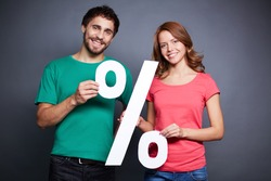 Portrait of young couple holding paper percentage sign and looking at camera