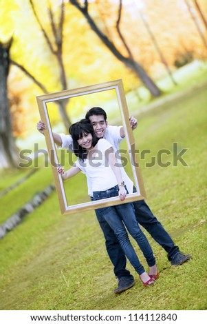 Portrait of young couple holding wooden frame. shout outdoor during autumn