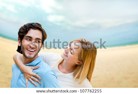 Portrait of young couple in love embracing at beach and enjoying time being together. Idealistic artistic photo poster for advertisement banner