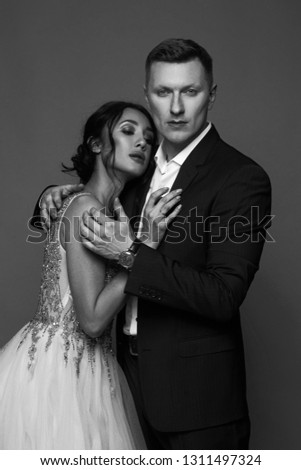 Portrait of young couple in love posing against gray backgound in studio dressed in classic clothes. Pretty woman in luxury dress tender hugging with handsome man #1311497324