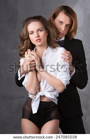 Portrait of young couple in love posing at studio dressed in classic clothes. Beauty and Fashion.