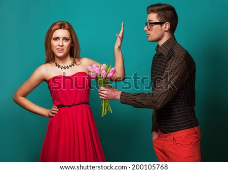 Portrait of young couple in love with flowers tulips posing at studio dressed in classic clothes