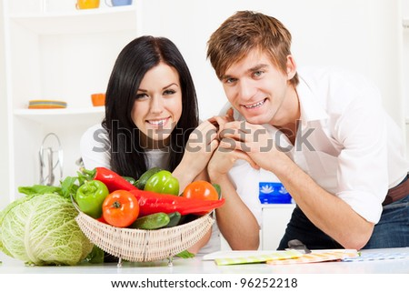 portrait of young couple in their kitchen happy smile, looking at camera