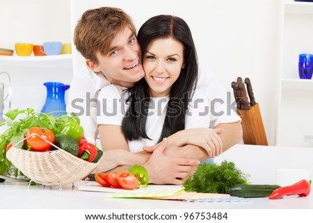 portrait of young couple in their kitchen hug, embracing happy smile, looking at camera