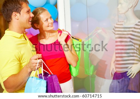 Portrait of young couple looking shop window in department store