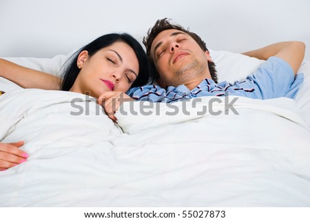 Portrait of young couple on bed sleeping together