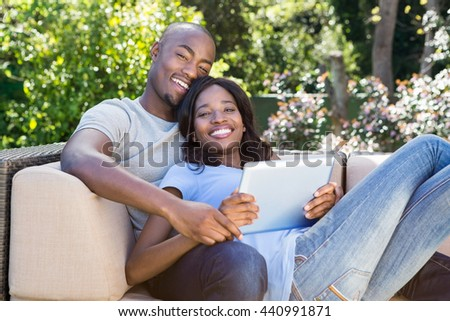 Portrait of young couple relaxing on the sofa and using digital tablet in the park