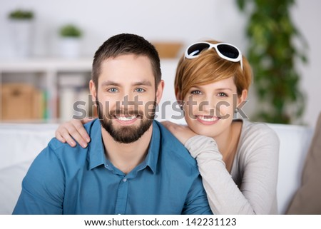 Portrait of young couple smiling together in house