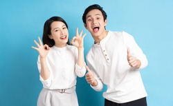 Portrait of young couple standing posing on blue background