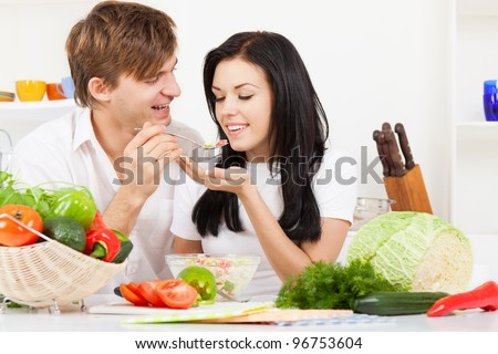 portrait of young couple tasting the meal in their kitchen happy smile, man feed woman with spoon, looking to each other