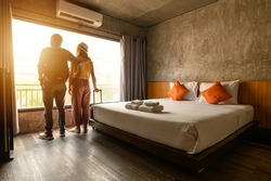 Portrait of young couple tourist standing nearly window, looking to beautiful view outside in hotel/resort bedroom after check-in. Conceptual of couple travel and vacation in their honeymoon period.