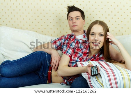 Portrait of young couple watching TV at home