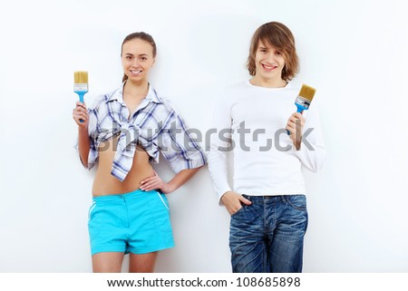 Portrait of young couple with paint brushes
