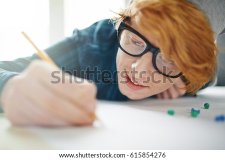 Portrait of young creative red haired man wearing beanie hat and glasses drawing with pencil leaning close to desk and smiling, enjoying work with inspiration