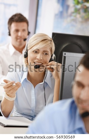 Portrait of young customer service operator talking on headset, smiling.?