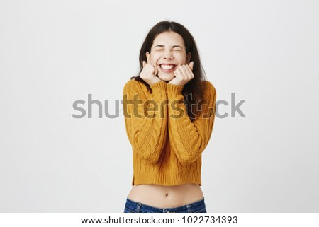 Portrait of young cute european student being overwhelmed with emotions, expressing excitement and happiness with closed eyes and hands near face while smiling broadly over gray background. #1022734393