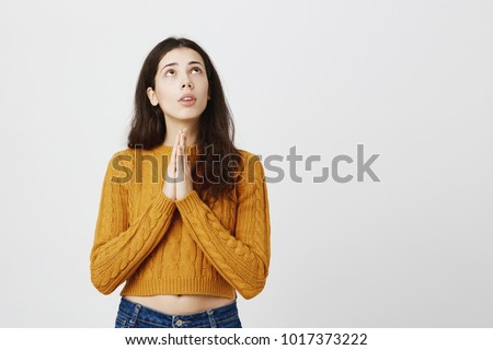 Portrait of young cute female student looking up with worried and determined expression, holding hands in pray, begging for something over gray background. Girl hopes that her dog will get better