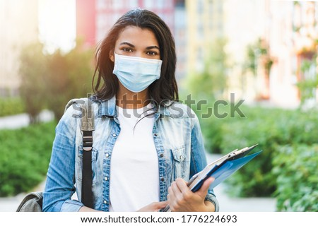Portrait of young dark skinned female student wearing medical mask posing outdoors with a backpack and pile of books.