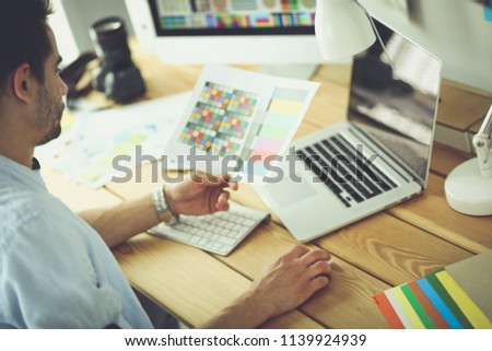 Portrait of young designer sitting at graphic studio in front of laptop and computer while working online