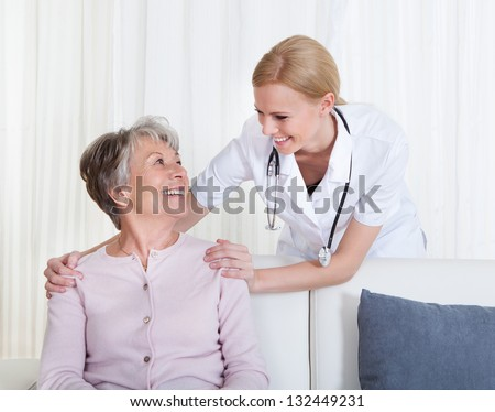 Portrait Of Young Doctor And Senior Patient Sitting On Couch