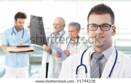 Portrait of young doctor looking at camera, smiling, medical team working in background.?