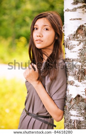 Portrait of young dreamy asian beautiful woman wearing grey dress standing near birch tree at summer green park.