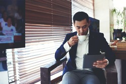 Portrait of young elegant men reading e-book on his digital tablet while drinking beverage in cafe inside, confident businessman using touch pad for remote work while enjoying rest during coffee break