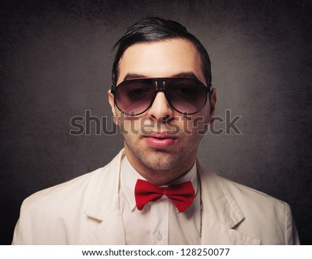 Portrait of young elegant nerd with sunglasses over grunge background.