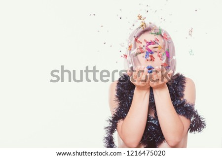 Portrait of young emotional attractive woman with garland, tinsel, blowing sequins to the camera objective, isolated on white background with copy space. Party time concept.