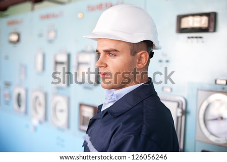 Portrait of young engineer with helmet at control room