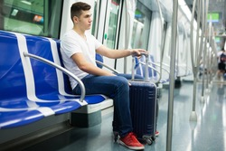 Portrait of young European man sitting in underground carriage and holding luggage bag